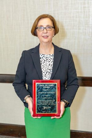 Deborah Johnson holding Hall of Fame plaque